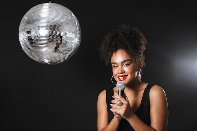 Belle femme africaine debout avec une boule disco argentée isolée sur un espace noir, tenant un microphone