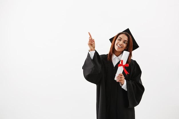Belle femme africaine diplômée souriant pointant le doigt dans le côté.