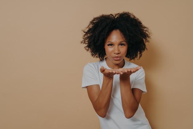 Belle femme africaine flirty bouclée en t-shirt blanc envoyant un baiser aérien et souriant, démontrant des sentiments chaleureux et de l'amour tout en posant en studio sur fond beige avec espace de copie pour le texte