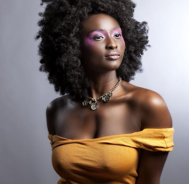 Belle femme africaine avec de grands afro bouclés et des fleurs dans ses cheveux