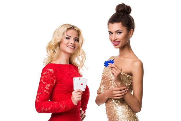 Belle femme africaine et jeune femme caucasienne aux longs cheveux blonds clairs en tenue de soirée. tenir des cartes à jouer et des jetons. isolé. poker