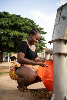 Belle femme africaine mettant de l'eau dans un seau