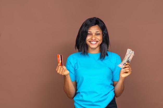 Belle femme africaine tenant de l'argent dans l'un et une carte de crédit dans l'autre