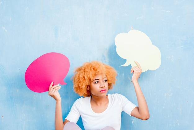 Belle femme africaine tenant des bulles réfléchies colorées sur le fond bleu du mur