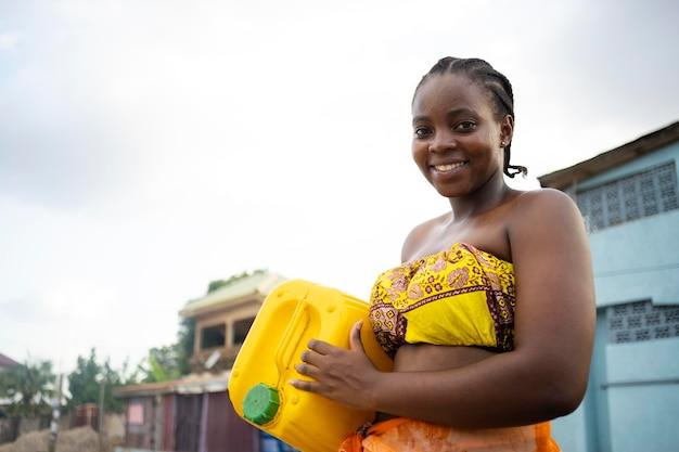 Belle femme africaine tenant un récipient d'eau