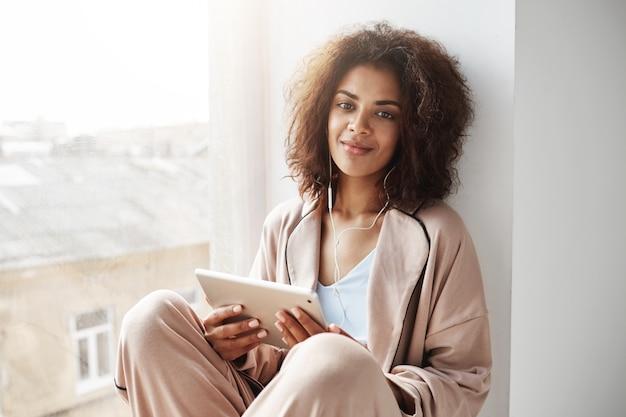 Belle femme africaine en vêtements de nuit et casque souriant tenant la tablette assis au rebord de la fenêtre.