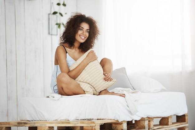 Belle femme africaine en vêtements de nuit souriant tenant un oreiller assis sur le lit à la maison.