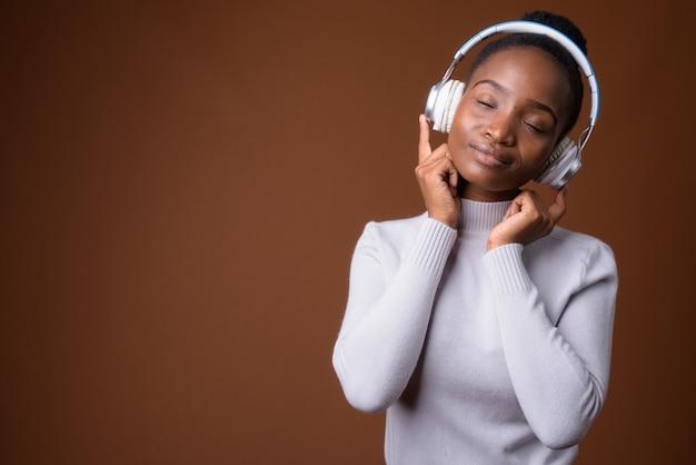 Belle femme africaine zoulou écoutant de la musique avec les yeux fermés