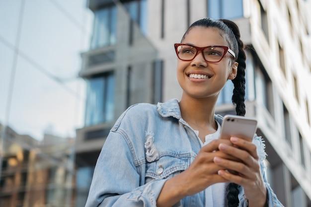 Belle femme afro-américaine à l'aide de téléphone portable, achats en ligne