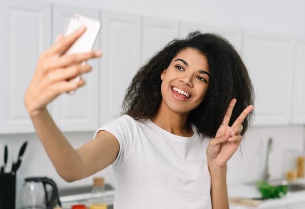 Belle femme afro-américaine à l'aide de téléphone portable, prenant selfie, montrant le signe de la victoire. blogger streaming vidéo en ligne