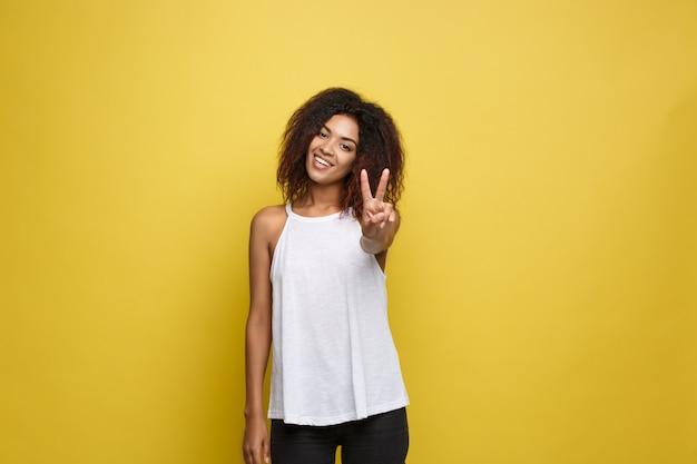 Belle femme afro-américaine attrayante posant jouer avec ses cheveux bouclés d'afro. fond d'écran jaune. espace de copie.
