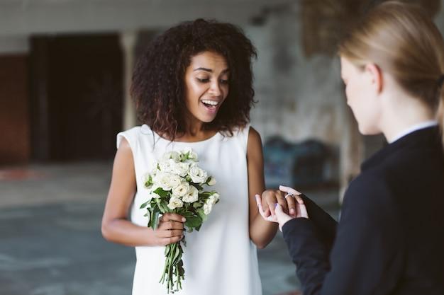 Belle femme afro-américaine aux cheveux bouclés foncés en robe blanche tenant petit bouquet de fleurs à la main tout en joyeusement sur la bague de mariage