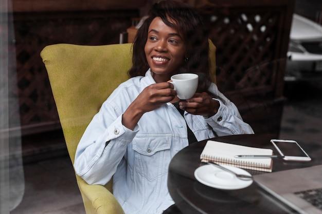 Belle femme afro-américaine buvant un café
