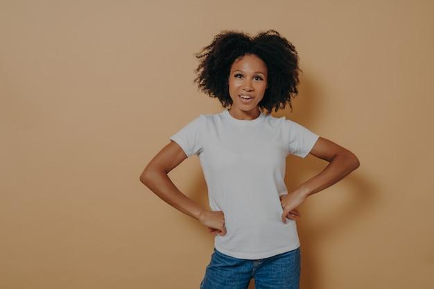 Belle femme afro-américaine confiante portant des vêtements élégants et décontractés en gardant les mains sur les hanches