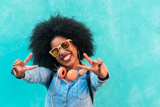 Belle femme afro-américaine faisant un signe de paix avec ses mains.