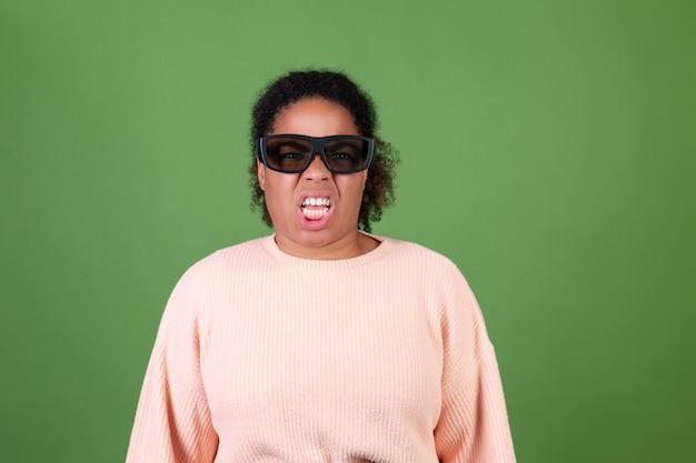 Belle femme afro-américaine sur un mur vert avec des lunettes de cinéma 3d regardant l'émotion de dégoût de film