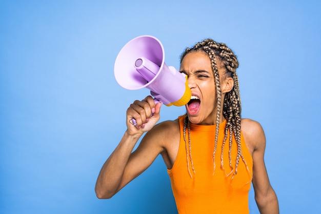 Belle femme afro-américaine avec des nattes et mégaphone sur mur coloré