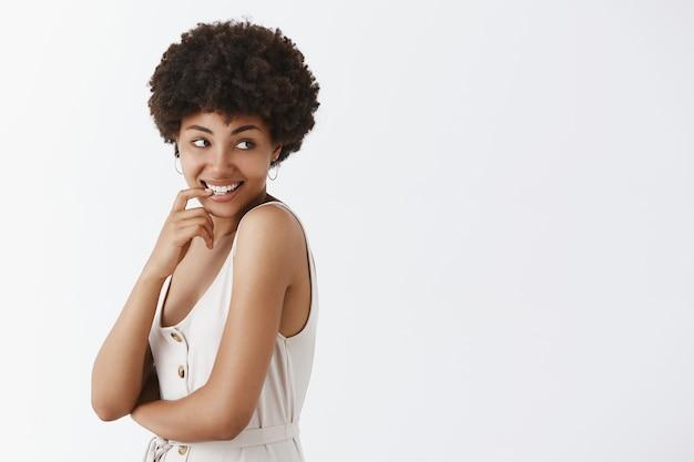 Belle femme afro-américaine sexy avec une coiffure afro tournant à droite avec plaisir et désir souriant, se mordant l'ongle avec une expression curieuse et intriguée