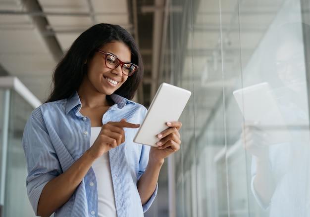 Belle femme afro-américaine souriante à l'aide de tablette numérique travaillant en ligne dans un bureau moderne