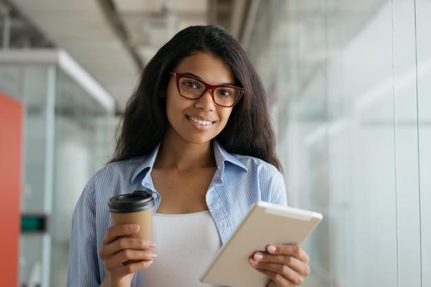 Belle femme afro-américaine souriante tenant une tasse de café et une tablette numérique à la recherche directe