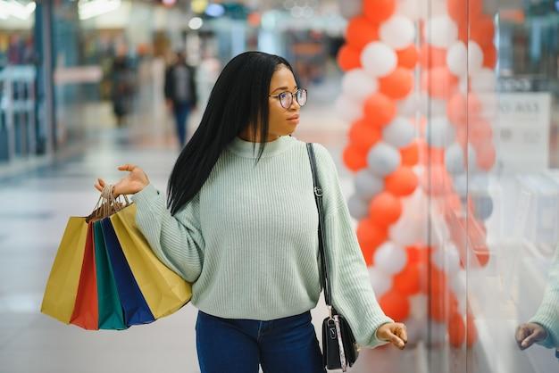 Belle femme afro-américaine tenant des sacs à provisions multicolores dans un magasin.