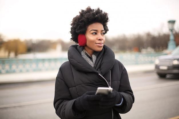 Belle femme afro, écouter de la musique sur le casque dans la ville