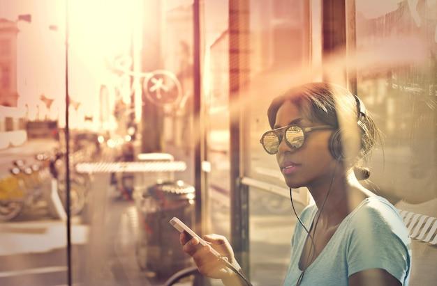 Belle femme afro, écouter de la musique sur des écouteurs