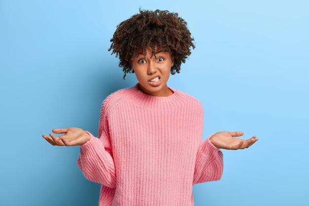 Belle femme avec un afro posant dans un pull rose