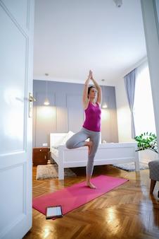 Belle femme d'âge moyen faisant du yoga dans sa maison