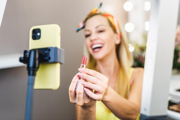 Belle femme d'âge moyen et maquilleuse de beauté professionnelle vlogger ou blogueur enregistrant un didacticiel de maquillage à partager sur le site web ou les médias sociaux.
