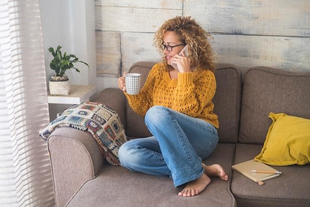 Belle femme d'âge moyen avec un pull jaune faire un appel téléphonique à la maison assise sur le canapé et boire du café