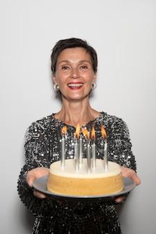 Belle femme d'âge moyen tenant un gâteau d'anniversaire