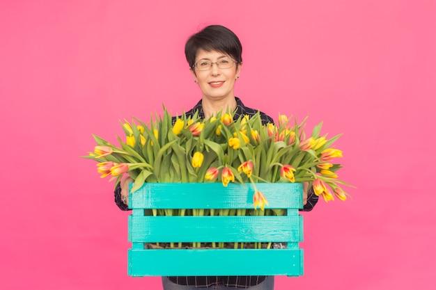 Belle femme d'âge moyen avec des tulipes jaunes sur fond rose. concept floristique, vacances et cadeaux