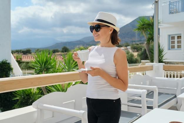 Belle femme d'âge moyen en vacances dans un hôtel spa resort, femme au repos avec une tasse de café