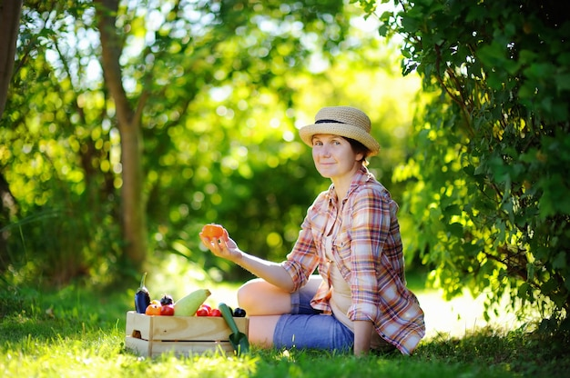 Belle femme d'âge mûr profiter de la récolte. jardinier femelle cueillant des légumes biologiques