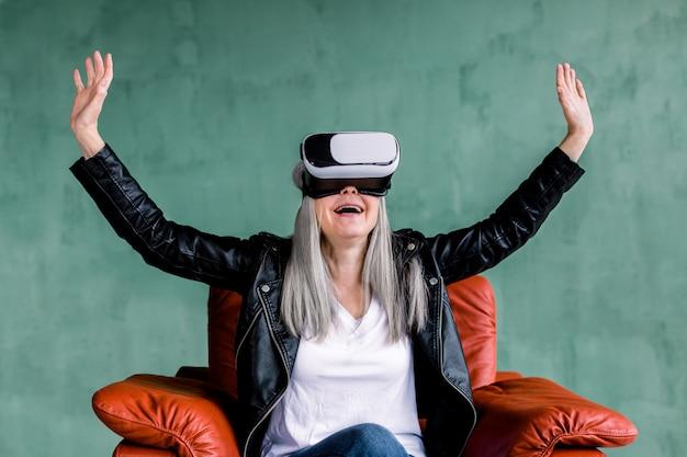 Belle femme âgée aux cheveux gris portant une veste en cuir noire, assis dans un fauteuil rouge confortable dans des lunettes de réalité virtuelle, touchant l'air avec ses mains