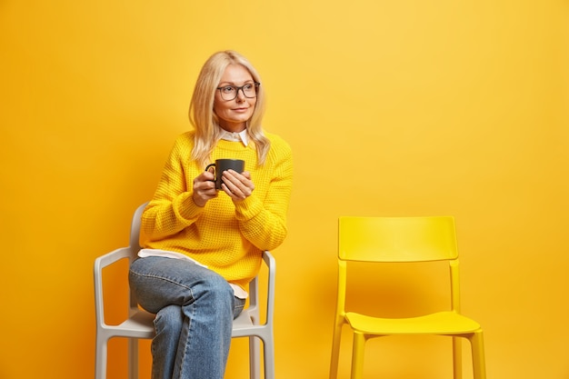 Belle femme âgée de cinquante ans jouit de temps libre pour de bons souvenirs boit du thé ou du café pose sur une chaise avec une expression réfléchie se souvient de toute la vie concentrée de côté. sérénité à la maison