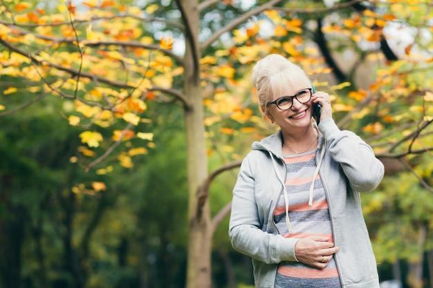 Belle femme âgée dans un sac à dos lors d'une promenade dans le parc, parler au téléphone