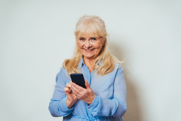 Belle femme âgée à la maison et regardant devant en souriant