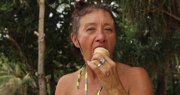 Belle femme âgée mordant une glace savoureuse et regardant la caméra