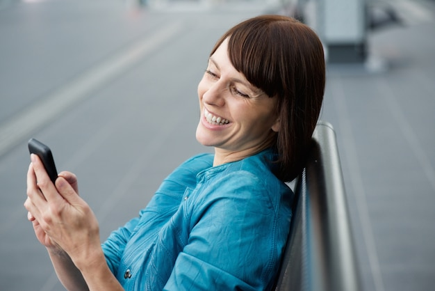 Belle femme âgée moyenne en regardant le téléphone portable