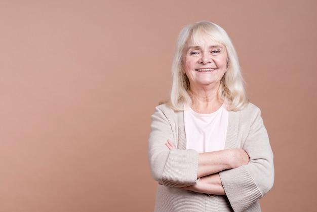Belle femme âgée souriante avec bras croisés