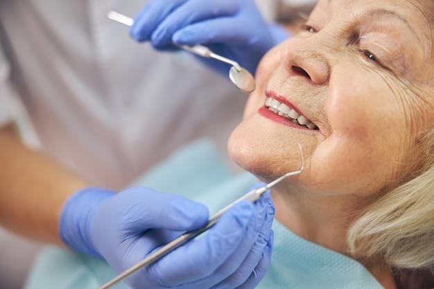 Belle femme âgée avec un sourire sain assis pendant la consultation avec un dentiste au cabinet dentaire