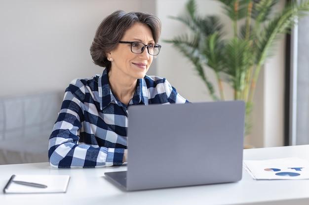 Belle femme âgée travaillant à distance à la maison sur internet à l'aide d'un ordinateur portable