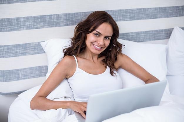 Belle femme à l'aide d'un ordinateur portable sur le lit