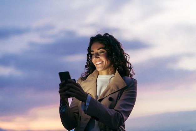Une belle femme à l'aide d'un smartphone avec un ciel nuageux violet