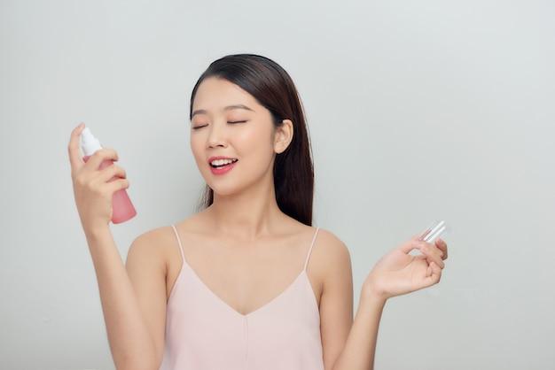 Belle femme à l'aide d'un spray pour le visage sur fond gris