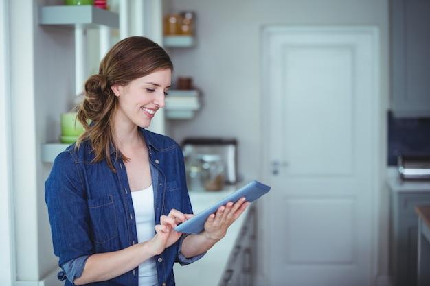Belle femme à l'aide de tablette numérique dans la cuisine
