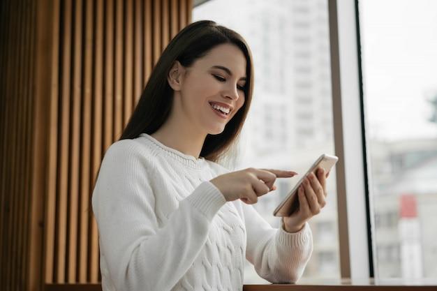 Belle femme à l'aide de téléphone portable, faire des achats en ligne, commander de la nourriture, rester à la maison