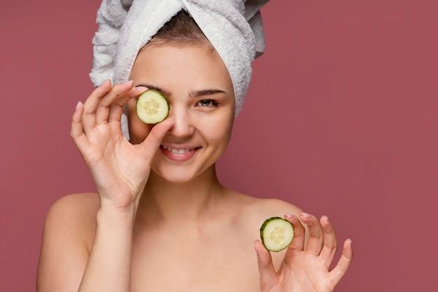 Belle femme à l'aide de tranches de concombre pour les yeux